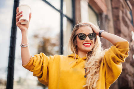 Photo pour Stylish happy young woman wearing boyfrend jeans, white sneakers bright yellow sweetshot.She holds coffee to go. portrait of smiling girl in sunglasses posing in the street - image libre de droit