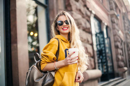 Photo pour young beautiful blonde drinking coffee walking around the city.mustard sweetshot.,urban backpack , bright red lips Posing against the window of the boutique Model looking aside and smile - image libre de droit