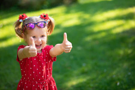 Foto de happy funny blonde little girl show sight thumbs up and good luck dressed in a bright red dress and sunglasses. Copy, empty space for text. - Imagen libre de derechos