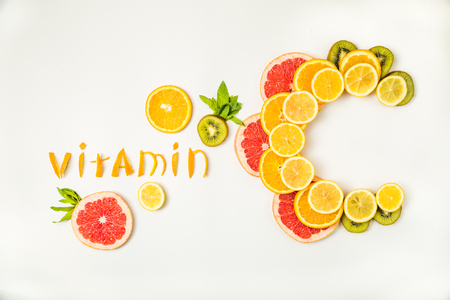 Photo pour Vitamin C letters made of citrus fruits - lemon, grapefruit, kiwi and orange slices on white background - image libre de droit
