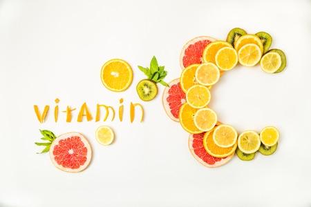 Photo pour Vitamin C letters made of citrus fruits - lemon, grapefruit, kiwi and orange slices on white background - image libre de droit