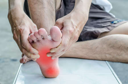 Foto per Pain in the foot. Massage of male feet. Pedicures. - Immagine Royalty Free