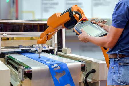 Foto de Engineers use a wireless remote control robot for gripping a workpiece out of the machine via a conveyor belt for smart factory, industry 4.0 concept - Imagen libre de derechos