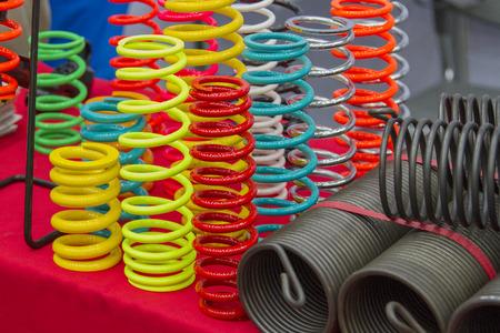 Foto de Coil springs are many colors on the red table. - Imagen libre de derechos