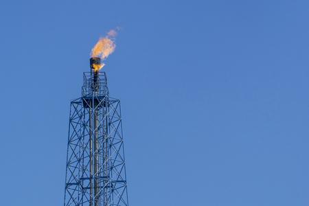Foto de Gas flares in petroleum refinery  with blue sky background  - Imagen libre de derechos