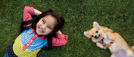 Foto de Happy Asian girl with her doggy portrait lying on lawn - Imagen libre de derechos