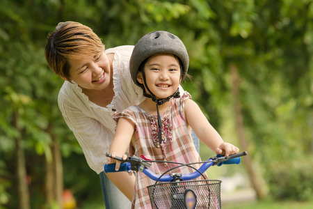 Photo for Little Asian child with mother practice to riding a bicycle - Royalty Free Image