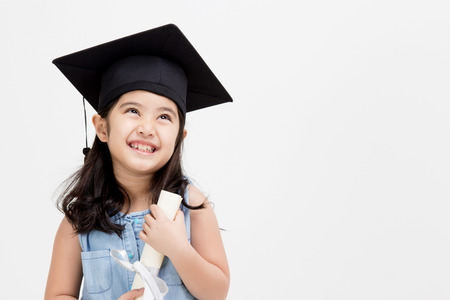 Photo for Happy Asian school kid graduate in graduation cap looking up - Royalty Free Image