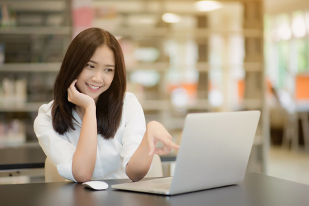 Photo pour Portrait of a happy beautiful Asian young woman using laptop in office - image libre de droit