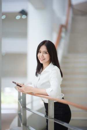 Photo for Young Asian woman executive working with a mobile phone in office building - Royalty Free Image