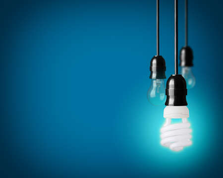 Foto de Light bulbs and energy saver bulb on blue background - Imagen libre de derechos