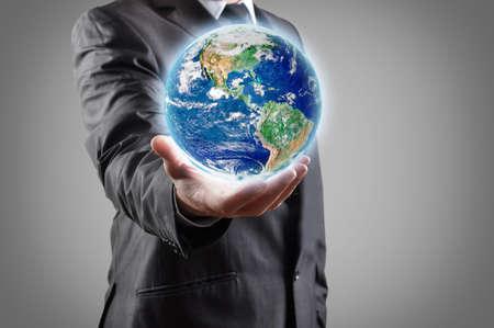 Photo pour Businessman holds earth in a hand  - image libre de droit