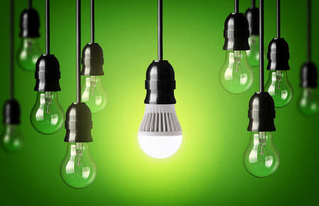 Foto de LED bulb and simple light bulbs Green background - Imagen libre de derechos