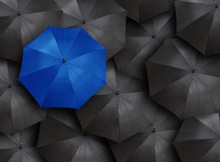 Foto de concept for leadership with many blacks and blue umbrella - Imagen libre de derechos