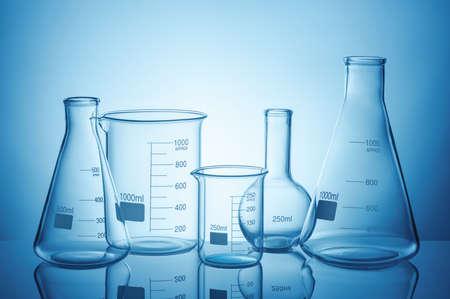 Foto de Laboratory glassware set with reflections on blue background - Imagen libre de derechos