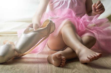 Photo for Little girl trying on ballet shoes - Royalty Free Image