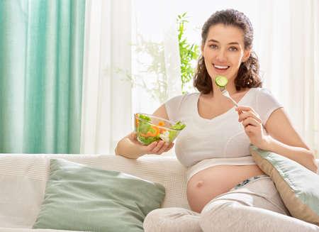 Photo pour happy pregnant woman eating salad - image libre de droit