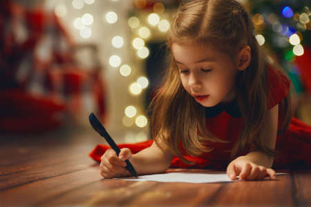 Photo pour small child writes the letter to Santa - image libre de droit
