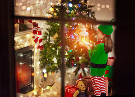 Photo for Little girl in costume of Christmas elf standing with a lantern in her hand by the Christmas tree - Royalty Free Image