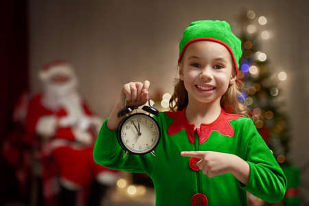 Photo for Happy child in Christmas elf costume with alarm. - Royalty Free Image