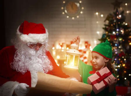 Photo for Ð¡ute elf helps Santa Claus reading wish list - Royalty Free Image