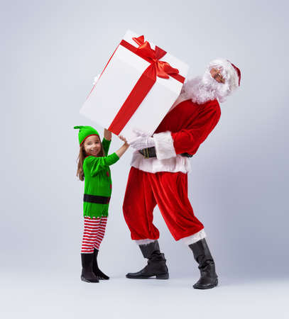 Photo for Funny Santa and elf holding together a large Christmas gift. - Royalty Free Image