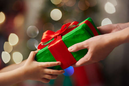 Photo pour Hands of parent giving a Christmas gift to child. - image libre de droit