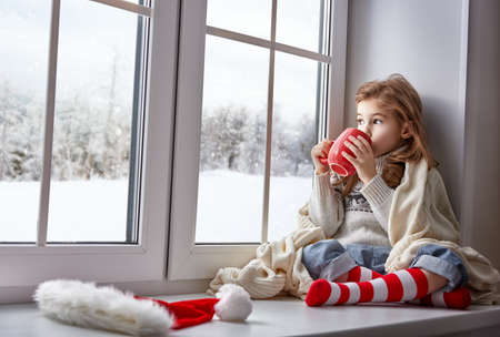 Foto de little girl sitting by the window with a cup of hot drink and looking at the winter forest - Imagen libre de derechos
