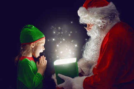 Photo for Cute little girl and Santa Claus opening a magic gift box. - Royalty Free Image