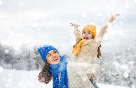 Foto de Happy family! Mother and child girl on a winter walk in nature. - Imagen libre de derechos