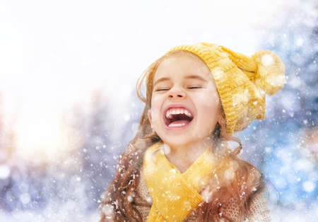 Photo pour Happy child girl playing on a winter walk in nature - image libre de droit