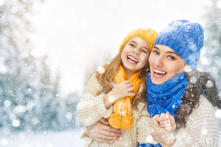 Foto de Happy family! Mother and child girl on a winter walk in nature. - Imagen libre de derechos