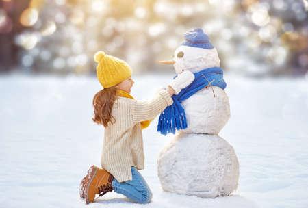Foto de Happy child girl playing with a snowman on a winter walk in nature - Imagen libre de derechos