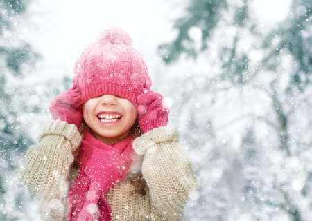 Foto de Happy child girl playing on a winter walk in nature - Imagen libre de derechos