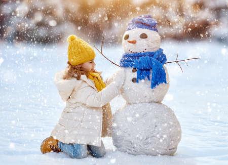 Foto de happy child girl plaing with a snowman on a snowy winter walk - Imagen libre de derechos