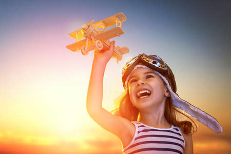 Photo pour dreams of flight! child playing with toy airplane against the sky at sunset - image libre de droit