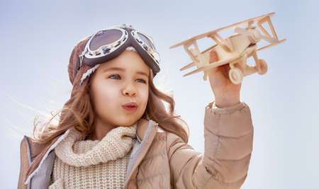 Foto de happy child girl playing with toy airplane. the dream of becoming a pilot - Imagen libre de derechos