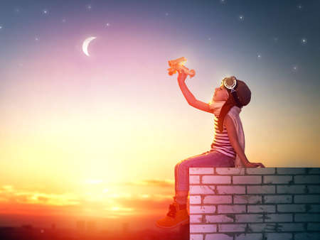 Foto de a child plays with a toy airplane in the sunset and dreams of becoming a pilot - Imagen libre de derechos