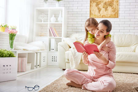 Photo pour pretty young mother reading a book to her daughter - image libre de droit