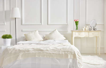Photo pour bedroom in soft light colors. big comfortable double bed in elegant classic bedroom - image libre de droit
