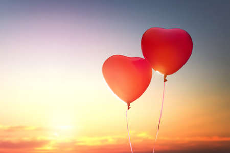 Photo for two red balloons in shape of heart on the background of sunset sky. the concept of love and Valentine's day. - Royalty Free Image