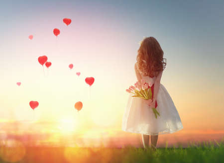 Photo pour Sweet child girl looking at red balloons. Little child girl holding bouquet of flowers. Balloons in shape of heart flying in the sunset sky. Wedding, Valentine, love concept. - image libre de droit