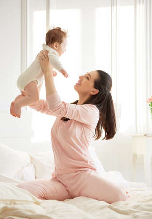 Foto de happy family. mother playing with her baby in the bedroom. - Imagen libre de derechos