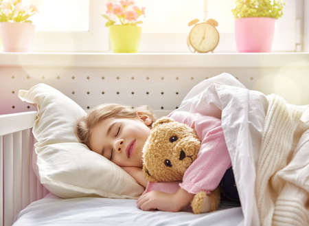 Photo pour Adorable little child girl sleeping in the bed with her toy. The child girl hugs the teddy bear. - image libre de droit