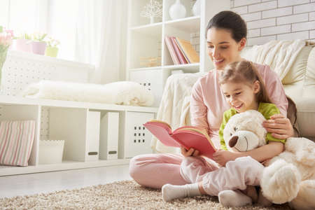 Photo for pretty young mother reading a book to her daughter - Royalty Free Image