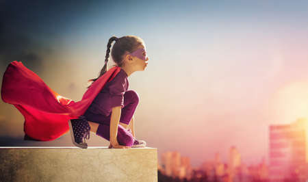 Photo for Little child girl plays superhero. Child on the background of sunset sky. Girl power concept - Royalty Free Image