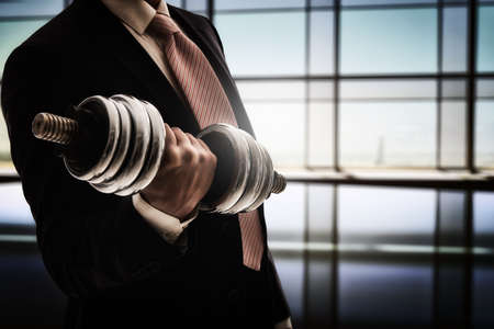 Foto de successful business man holding a heavy dumbbell. the concept of success in a hard work of business. - Imagen libre de derechos