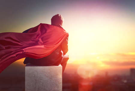 Foto de superhero businessman looking at city skyline at sunset. the concept of success, leadership and victory in business. - Imagen libre de derechos
