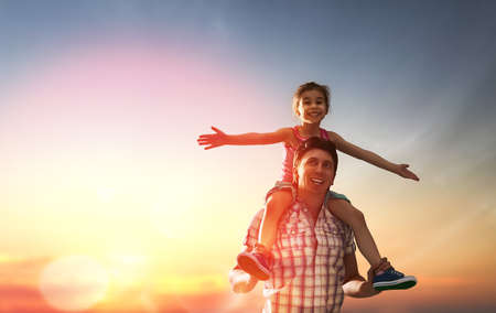 Foto de happy family at sunset. father and daughter having fun and playing in nature. the child sits on the shoulders of his father. - Imagen libre de derechos