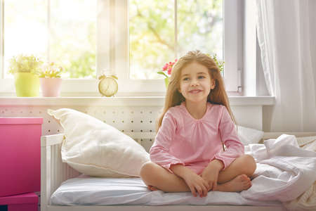 Photo for The child girl woke up and enjoys the morning sun. - Royalty Free Image